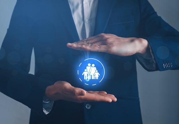 Бизнесмен руки с защитным жестом и значком семья. концепция семейного страхования.
