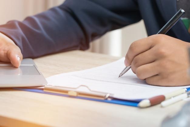 ビジネスマンの手の仕事とコンピューター、仕事場、事業報告書、未完成の文書の山の上の情報を検索するための紙のファイルのスタックの作業と書き込み