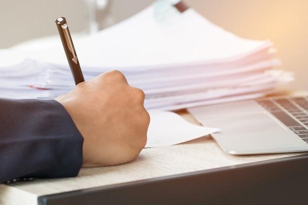 ビジネスマンの手の仕事とコンピューター、情報を検索する紙のファイルのスタックにデータを書き込む