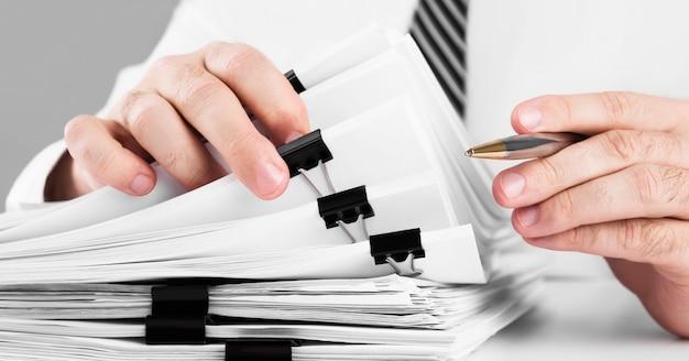 ビジネスデスクのホームオフィス、ビジネスコンセプトの情報を検索するための紙のファイルのスタックで作業するビジネスマンの手。