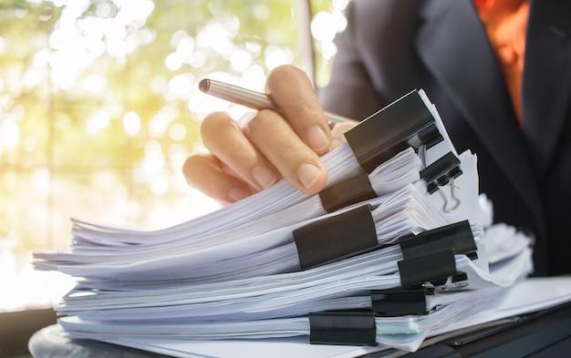 ビジネスマンの手で働く情報を検索するための紙ファイルのスタック