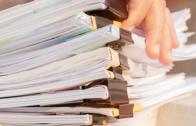 Businessman hands working in many documents stacks folders in office for annual report