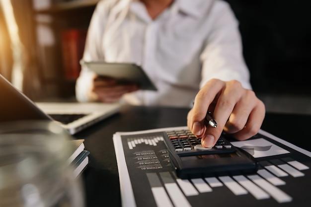 ビジネスマンは、朝の光の中でオフィスでコストと計算機とタブレット、スマートフォンを備えたラップトップについての財政で働いています