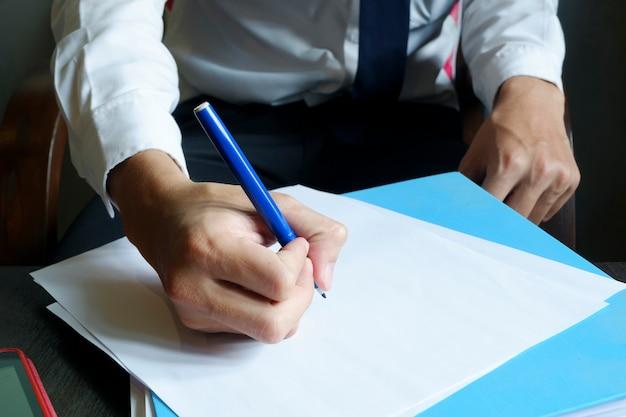Businessman hands writing on paper , freelancer man working, filtered image, cross process, flare sun light