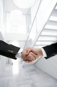 Businessman handshake on modern white office
