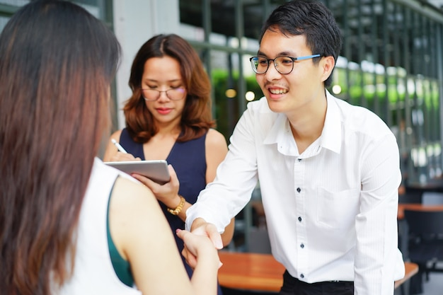 Businessman handshake with businesswoman after deal successful