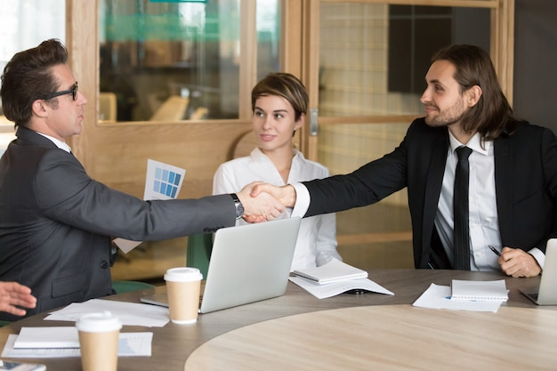 Businessman handshaking new colleague during team meeting