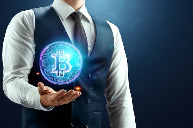 A businessman has a bitcoin hologram in his palm