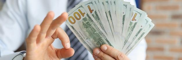 사업가 초침으로 그의 손에 100 달러 지폐가 제스처 확인을 보여줍니다 프리미엄 사진