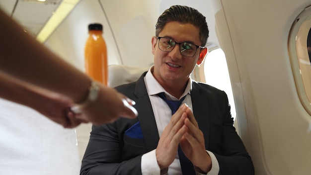 ビジネスマンは飛行機の中でスチュワーデスがオレンジジュースを出している。出張旅行のコンセプト。