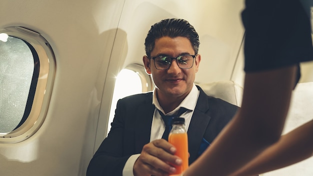 ビジネスマンは飛行機の中でスチュワーデスによって提供されるオレンジジュースを持っています