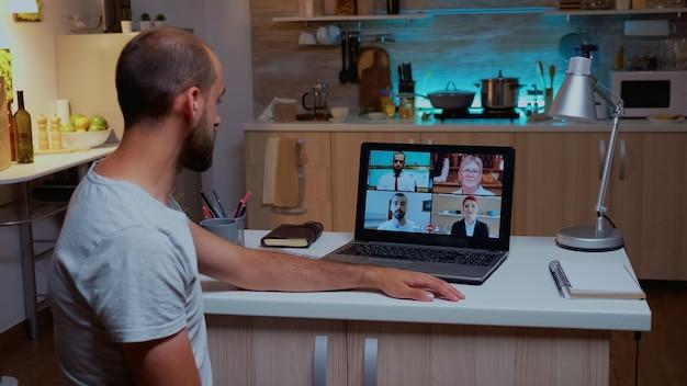 Бизнесмен, имеющий видеоконференцию с командой в полночь, используя ноутбук на домашней кухне. корпоративная встреча с использованием современных технологий беспроводной сети, разговор по веб-камере в полночь