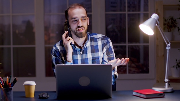 사업가가 밤 시간에 집에서 일하는 동안 전화로 논쟁을 하고 있습니다.