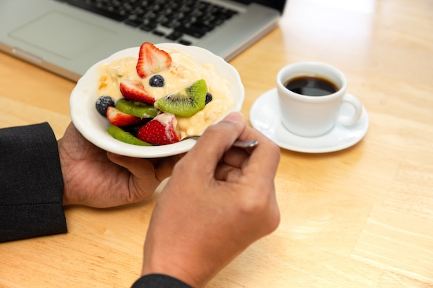 Businessman having bowl of fresh fruits salad with yogurt and coffee and laptop