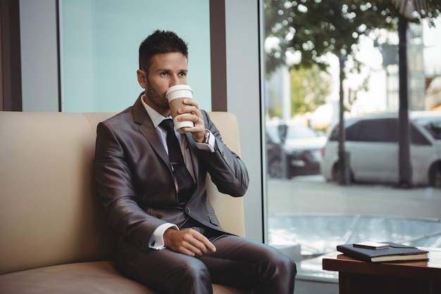 Uomo d'affari che mangia caffè mentre sedendosi sul sofà