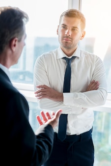 Businessman having conversation with his male partner in office