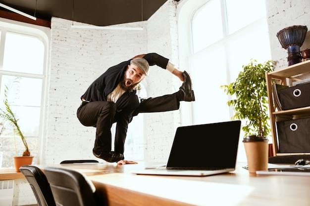 職場のオフィスでブレイクダンスを楽しんで踊るビジネスマン