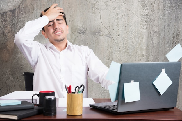 Бизнесмен, имеющий головную боль за офисным столом.