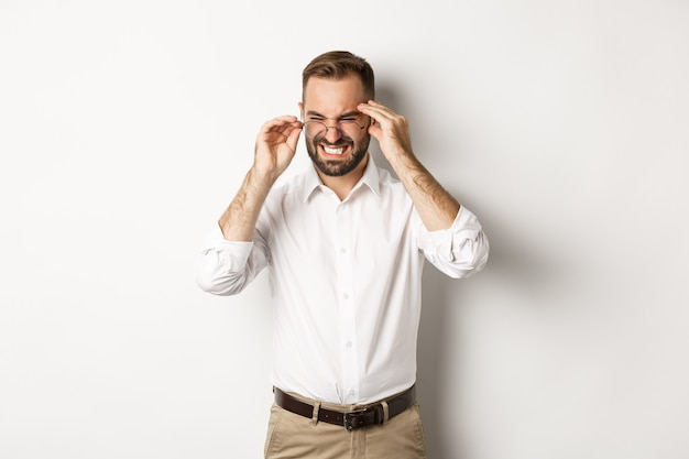 Businessman having headache, grimacing and holding hands on head, standing over white background.