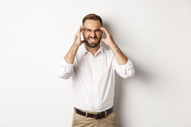 Uomo d'affari che ha mal di testa, smorfie e mano nella mano sulla testa, in piedi