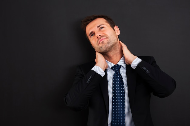 Businessman having pain in the neck