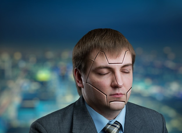 Businessman head with cracks on his face on city background