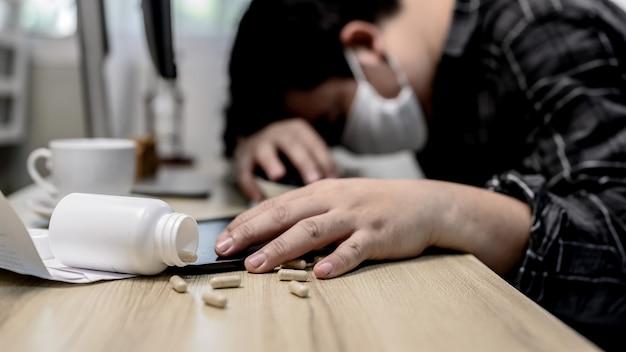 ビジネスマンの頭痛と薬を服用します。失業とメンタルヘルスの問題。心的外傷後ストレス障害(ptsd)。アジアの労働者の経済問題。