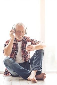 Businessman in headphones is listening to music