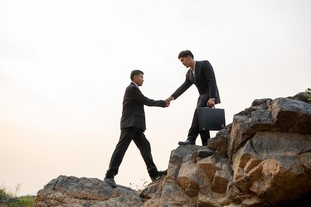 일몰 배경, 비즈니스 팀워크 성공 개념에서 산을 하이킹 서로 돕는 사업가.