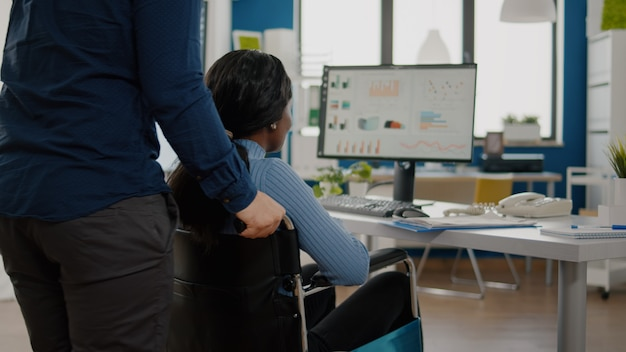 휠체어를 밀고 회사 사무실에 들어오는 장애인 흑인 동료를 돕는 사업가 ...