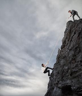Бизнесмен помогает другому мужчине подняться на гору. бизнесмены сотрудничают для достижения цели.