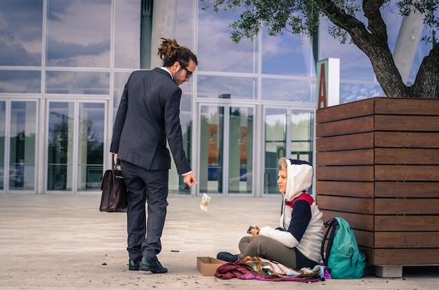 Businessman helps a homeless giving money - business, people and lifestyle concept - caucasian people