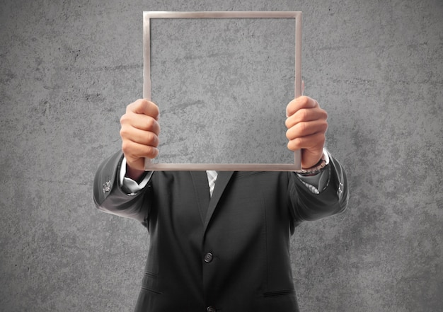 Businessman hiding his face with a frame
