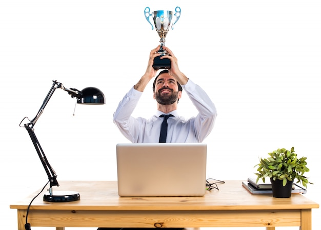 Businessman in his office holding a trophy