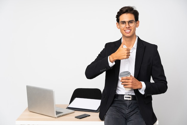 Businessman in his office over isolated white wall giving a thumbs up gesture