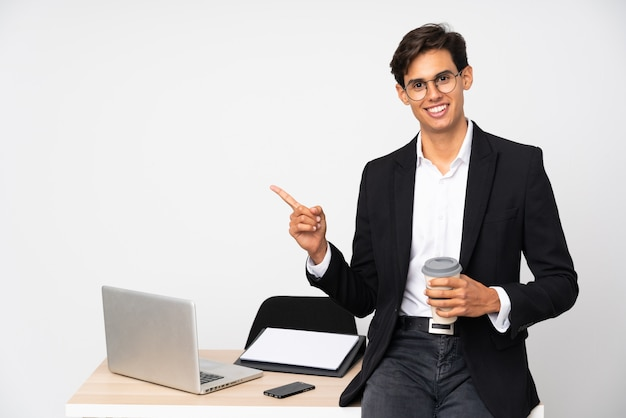 Businessman in his office over isolated white wall pointing finger to the side