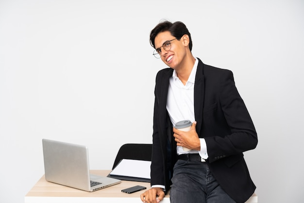 Businessman in his office laughing and looking up