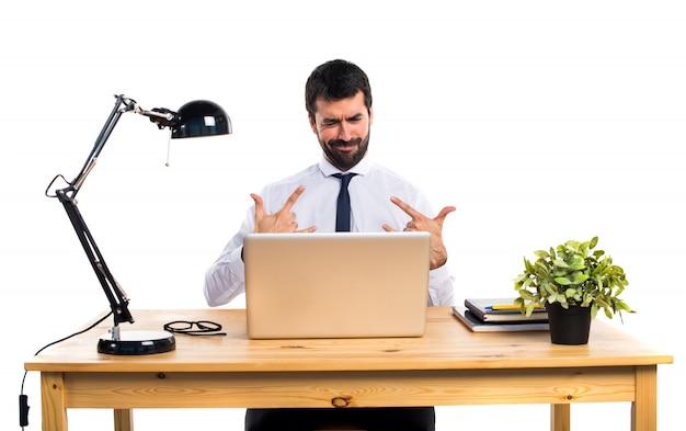 Uomo d'affari nel suo ufficio facendo gesto di corno