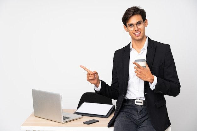 Businessman in his office pointing finger to the side