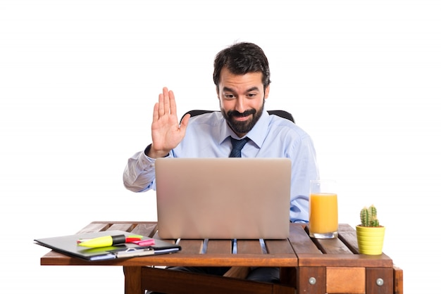 Businessman in his office saluting somebody