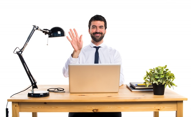 Businessman in his office saluting