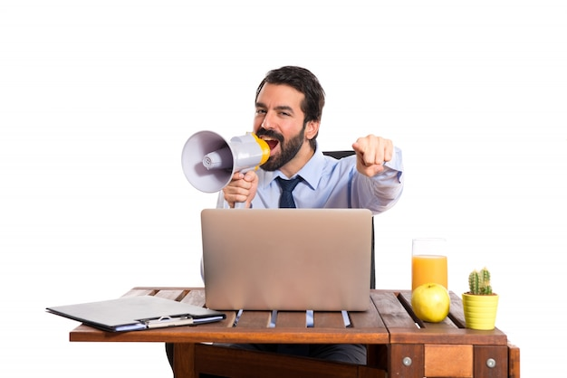 Businessman in his office shouting by megaphone