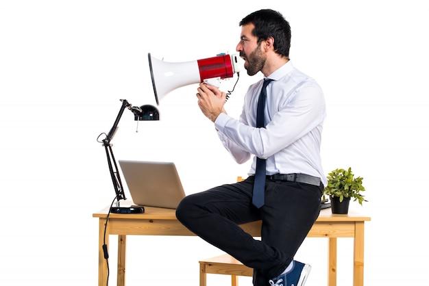 Uomo d'affari nel suo ufficio gridando dal megafono