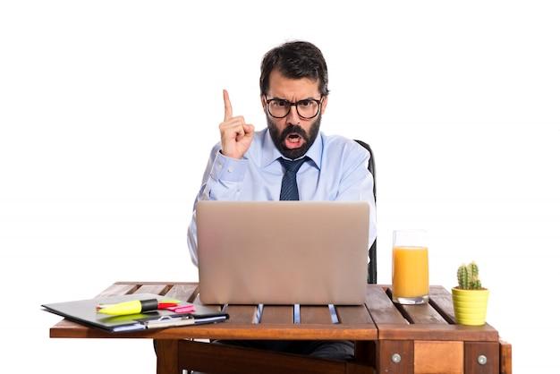 Uomo d'affari nel suo ufficio gridando su sfondo bianco
