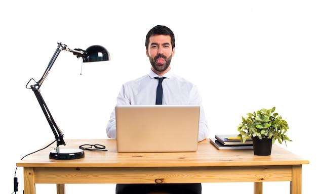 Uomo d'affari nel suo ufficio prendendo la sua lingua