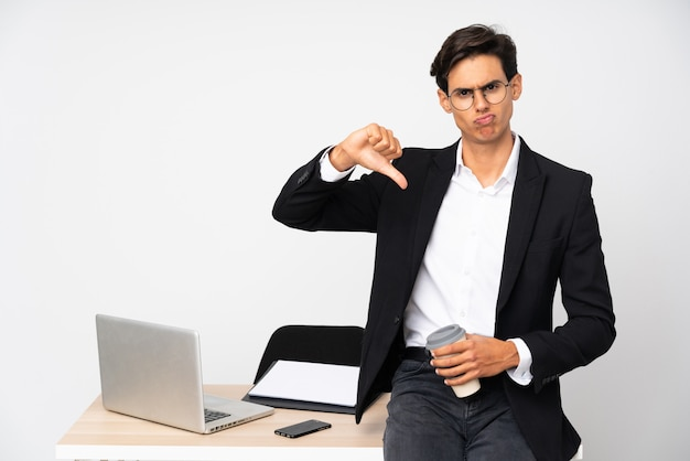 Businessman in his office over white wall showing thumb down sign