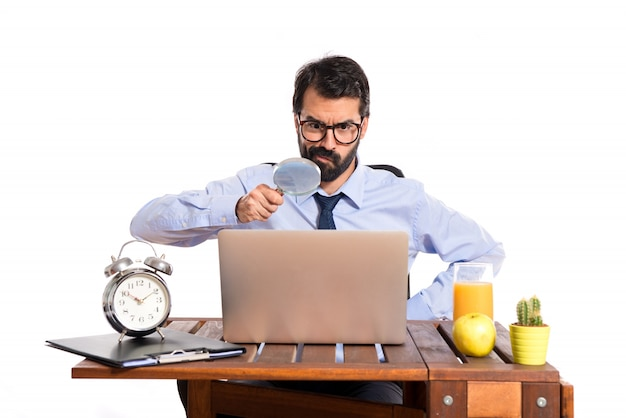 Businessman in his office with magnifying glass