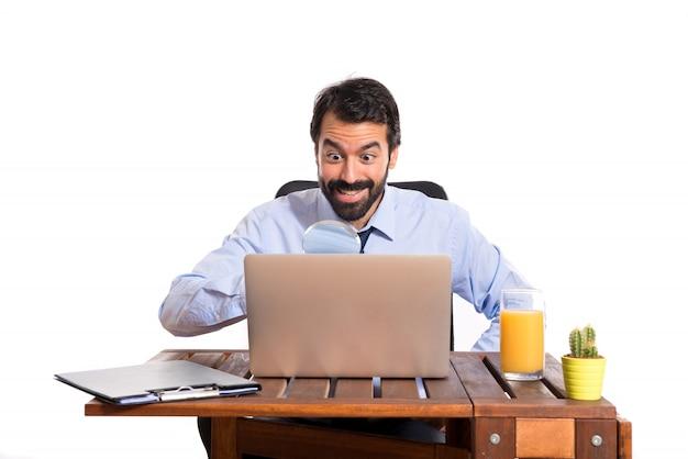 Uomo d'affari nel suo ufficio con lente d'ingrandimento