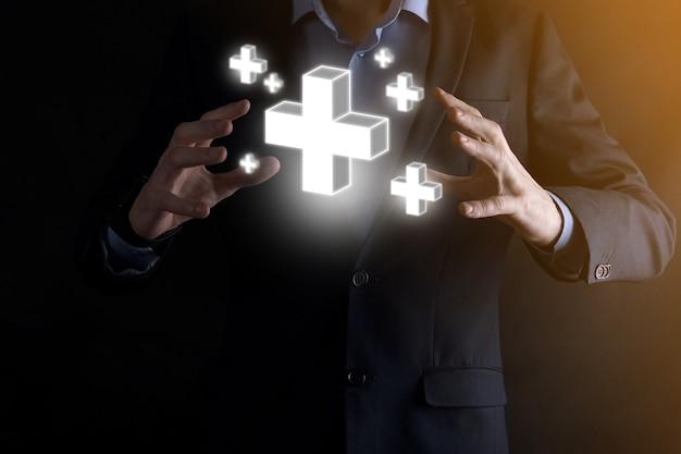 ビジネスマンは3dプラスアイコンを保持し、男性は手に持って利益、利益、開発、プラス記号で表されるcsrなどの肯定的なものを提供します。手はプラス記号を示しています