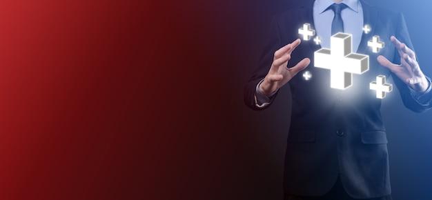 Бизнесмен держит значок 3d плюс, человек, держащий руку, предлагает положительные вещи, такие как прибыль, преимущества, развитие, ксо, представленные знаком плюс. рука показывает знак плюса.